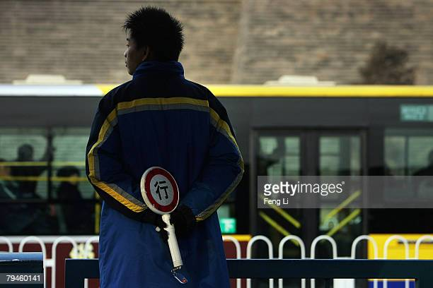 A warden monitors traffic at a bus stop on January 13 2008 in Beijing China Beijing will host Games of the XXIX Olympiad from August 8 to 24 2008