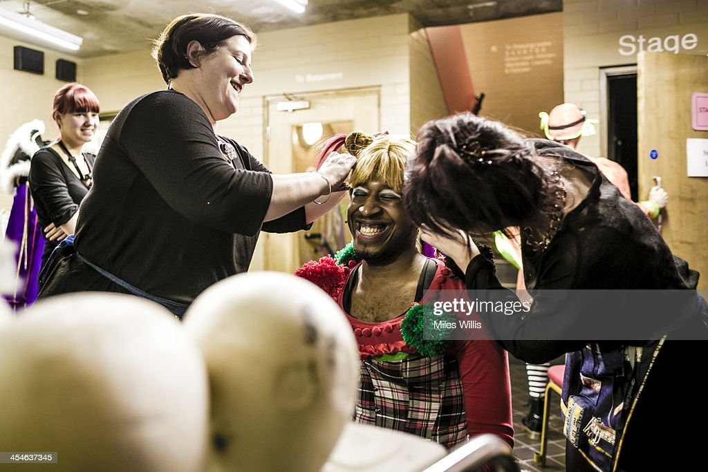 Wardrobe and a make up artist help Darren Hart playing 'Jester' make a costume change during the Puss in Boots pantomime at the Hackney Empire on December 6, 2013 in London, England.