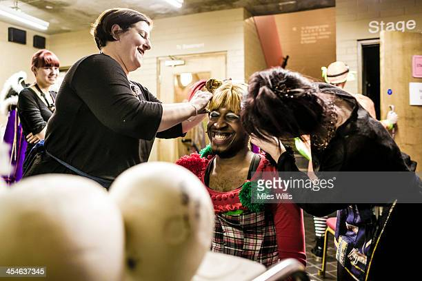 Wardrobe and a make up artist help Darren Hart playing 'Jester' make a costume change during the Puss in Boots pantomime at the Hackney Empire on...