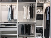 A well-organized closet. All things in their places, in boxes. Capsule wardrobe. Storage system.