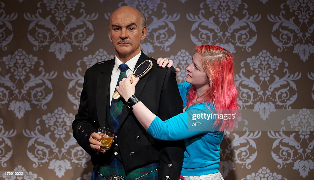 Wardrobe assistant Jane Anderson poses as she brushes a wax figure of British actor Sean Connery wearing a traditional Scottish kilt to mark his 83rd birthday on August 25 during a photo call at Madame Tussauds in central London on August 19, 2013.