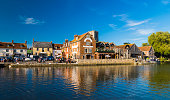 The old buildings and churches are reflected in the river Frome at Wareham in Dorset