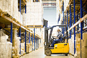 Serious busy young warehouse driver operating forklift to put heavy packaged boxes on shelf