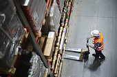 Above view of warehouse loader using forklift cart to pick up pallet with goods