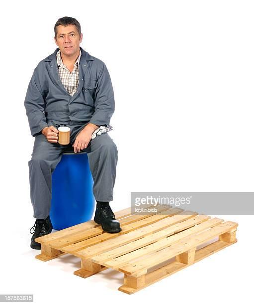 Magazzino uomo seduto sul tamburo avendo una pausa