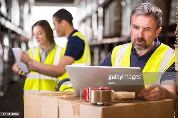 warehouse manager checking deliveries on his laptop