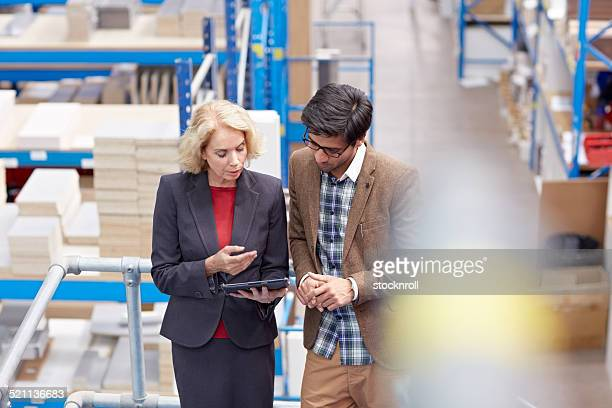 Warehouse manager checking something with her supervisor