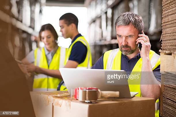 warehouse manager ringing a supplier