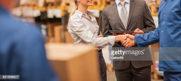 Warehouse manager shaking hands with worker