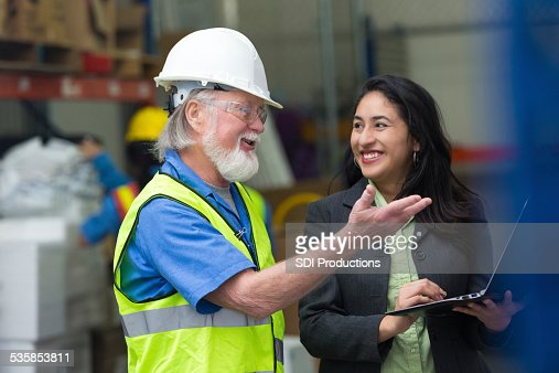 Warehouse manager taking inventory with female supervisor