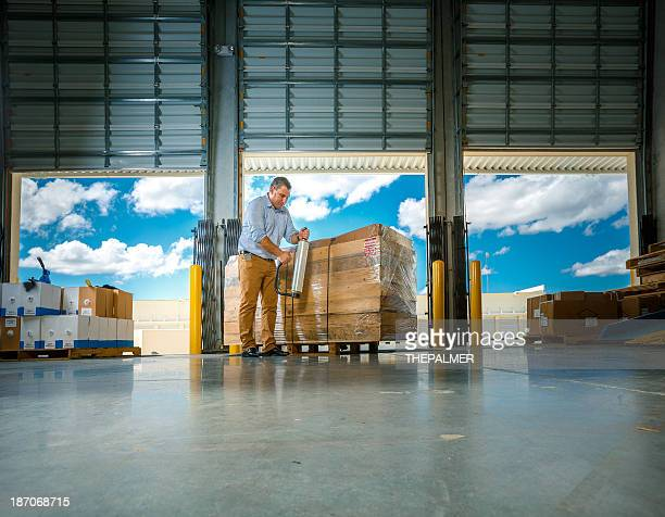 warehouse manager wrapping merchandise