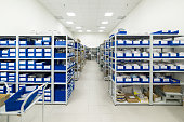 Warehouse of components for the electronics industry. White metal racks with blue plastic trays installed in them.