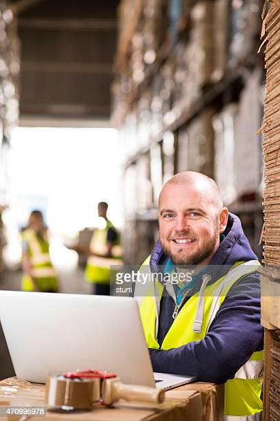 warehouse Vorgesetzten, lächelt in die Kamera.