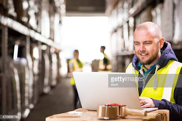 warehouse superviseur souriant tout en vérifiant les commandes en ligne