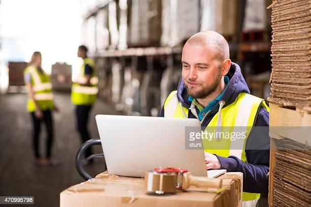 warehouse supervisor smiling whilst checking online orders