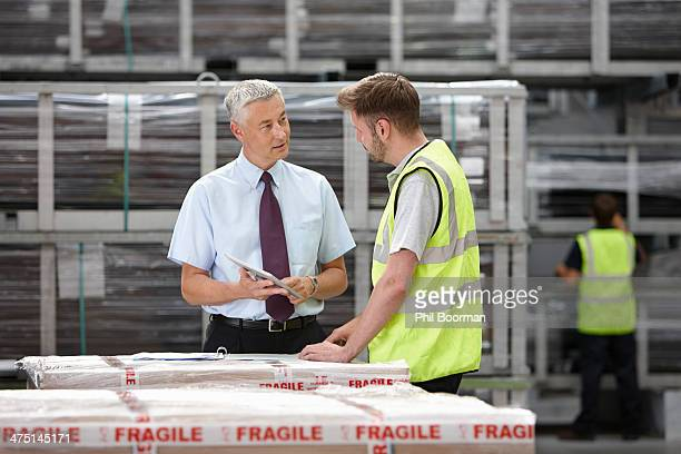 Warehouse worker and manager discussing order in engineering warehouse
