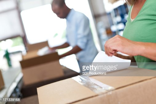 Warehouse worker attaching label onto box being shipped