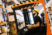 Warehouse industry worker doing logistics work with forklift loader