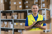 Warehouse worker holding clipboard in a large warehouse. Mature man looking up order details on a clipboard as he shops in a hardware warehouse for supplies , close up upper body