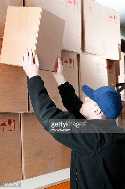 Warehouse worker moves a cardboard box