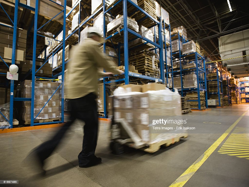 Warehouse worker pushing palette : Stock Photo