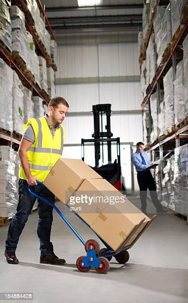 Warehouse de Travailleur avec un camion à la main