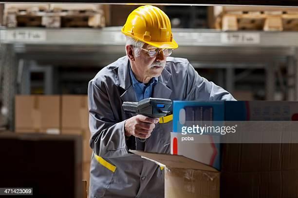 warehouse  worker, warehouseman scanning cardboard box with bar code reade
