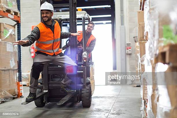 Warehouse workers surfing wit the forklift