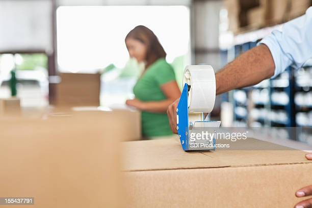 Warhouse worker assembling package close up on tape dispenser