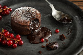 A single serving of warm chocolate lava cake sprinkled with powdered sugar with a bite taken out. The molten chocolate center spills out through the hole in the cakey wall. Red currant berries are the