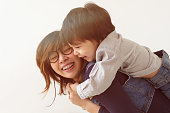 Japanese mother hugs her son, they laugh and smile.