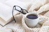 Warm knitted plaid, glasses, cup of hot coffee and book on wooden table. Autumn and winter, leisure concept