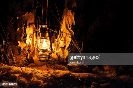 Warm oil lamps light in the snow : Stock Photo