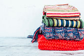 Warm woven scarves of bright colors lying in stack on wooden table