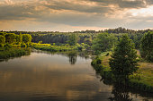warm summer evening. beautiful view of the river with grassy coasts, trees and dense forest under the cloudy sky in the warm sunset lighting