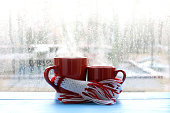 big and small red cup wrapped in a scarf on window background with drops after the rain