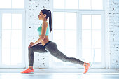 Side view of young beautiful young woman in sportswear doing stretching while standing in front of window at gym