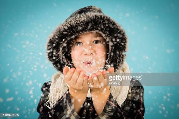 Warm angezogen kleines Mädchen Blasen Handvoll Schnee