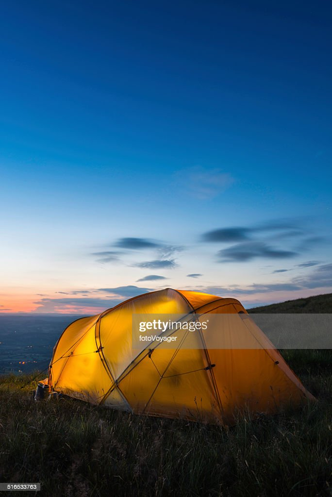 Warmly illuminated dome tent camped on mountain at sunset