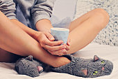 Woman wearing cozy warm wool socks close up. Warmth concept. Winter clothes