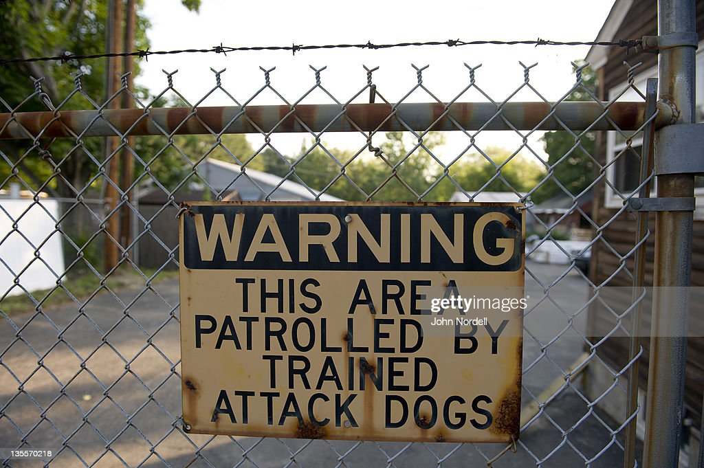 Warning attack dog sign on a fence topped with barbed wire