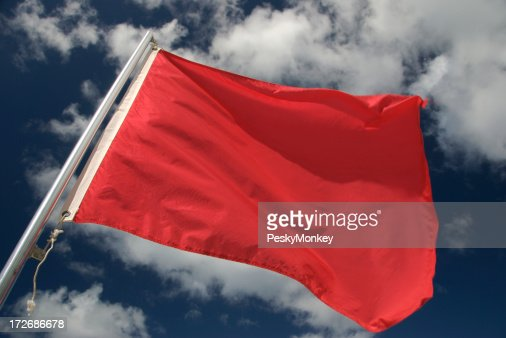 Warning Red Flag Waving in the Wind Blue Sky Clouds