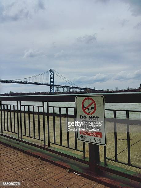 Warning Sign Board Hanging On Railing At Harbor By River Against Cloudy Sky