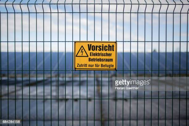 Warning sign 'Caution Electric fence' on a fence In the background you can see a solar field on April 11 2017 in Gross Doelln Germany