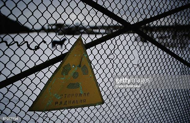 A warning sign for radiation is seen on a fence in front of a field housing remnants of highly radiated machinery and transportation vehicles used...