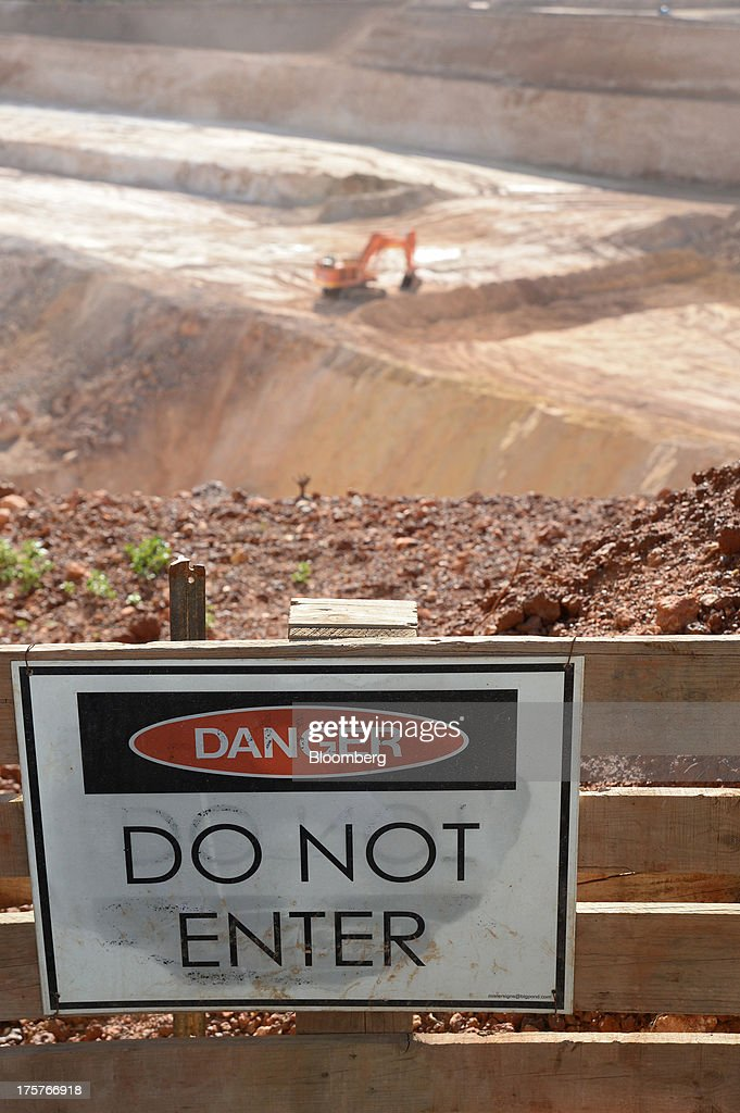 A warning sign hangs on a fence in front of the open mine pit at the Norton Gold Fields Ltd. Enterprise operations 68 kilometers north-west of Kalgoorlie, Australia, on Wednesday, Aug. 7, 2013. Norton, the Australian producer controlled by China's Zijin Mining Group Co., is seeking further acquisition targets as falling prices cut the value of mines. Photographer: Carla Gottgens/Bloomberg via Getty Images