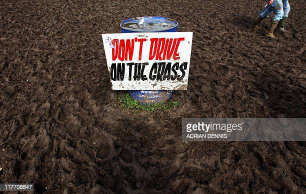 A warning sign is seen on what was once a grassy area while festivalgoers walk past at the Glastonbury festival near Glastonbury Somerset on June 25...