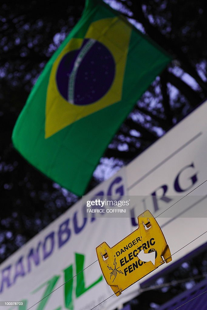 A warning sign is seen underneath a Brazilian falg at the top of the gate of the Randburg High School, on May 24, 2010 in Johannesbrug. Randburg High School will be the Brazil training centre during the upcoming FIFA Football World Cup in South Africa.
