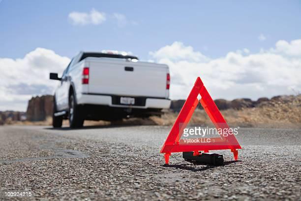 Warning sign on road behind broken down truck
