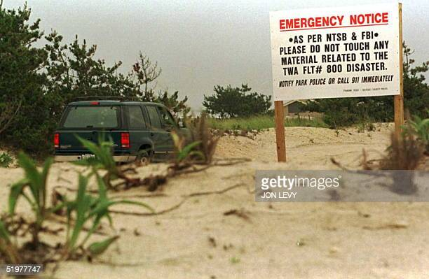 A warning sign on the dunes alerts beach goers 25 July to watch for debris washed ashore from downed TWA flight 800 at Smith's Point Long Island New...